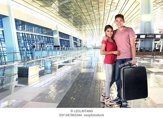 Smiling asian couple holding luggage bags to traveling at airport