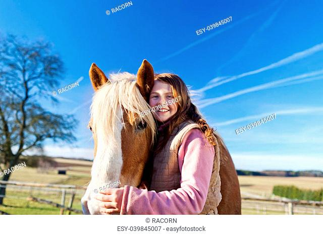 Loving portrait of a girl and her horse outdoors on a bright sunny day