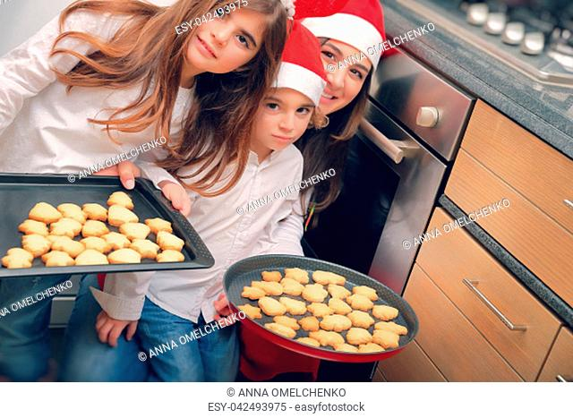 Happy mother with two cute kids baking tasty sweet homemade cookies, gingerbread, traditional Christmas sweets, good Christmastime family tradition