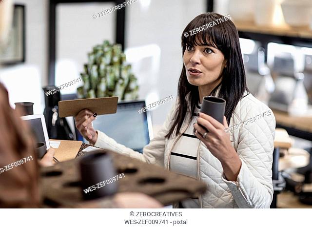Woman holding handcrafted objects talking