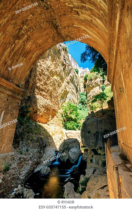 Wall of The New Bridge - Puente Nuevo is the 120-metre deep chasm that carries the Guadalevin River and divides city of Ronda, Province Of Malaga, Spain