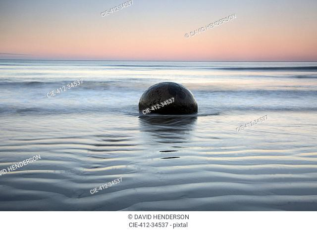Tranquil rippling seascape and boulder, Moeraki Boulders, South Island, New Zealand