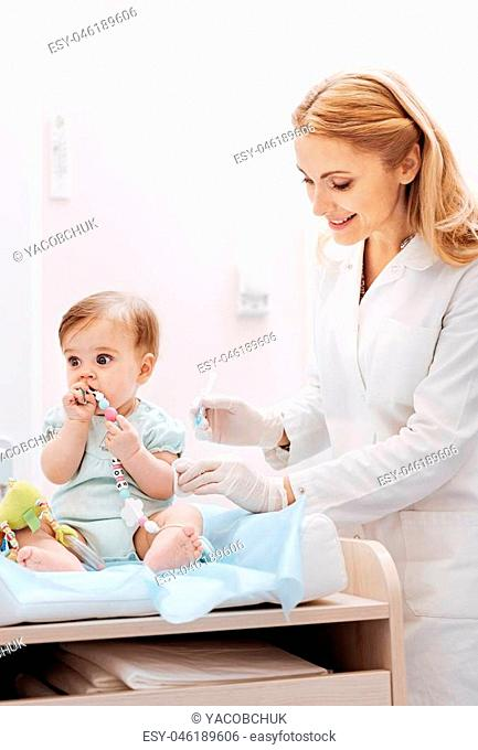 Wait a second. Charming baby girl looking forward playing with toy sitting near nurse