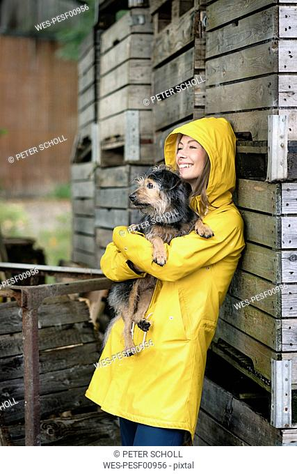 Smiling woman on a farm standing at wooden boxes holding dog