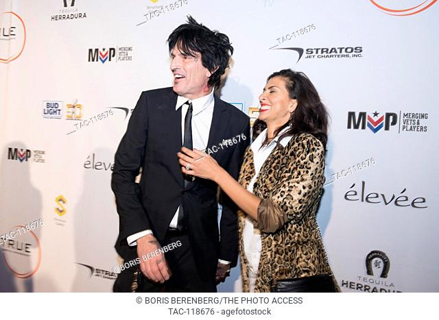 Tommy Lee poses with his fiance Sofia Toufa for a photo at the Glazer Palooza + Suits & Sneakers Red Carpet event on February 3rd at Pier 27 in San Francisco