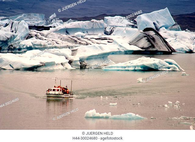 Iceland, Jokulsarlon Glacial Lagoon , Icebergs melting, sunset, near activ vulcano Vatnajoekull, tourist boat