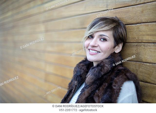 Portrait of a stylish woman outdoors smiling at camera