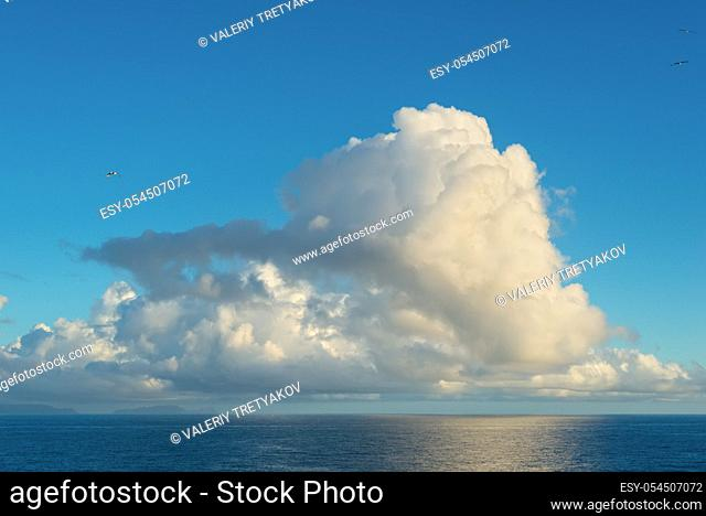 Blue sky with clouds over sea at sunset. Nature composition