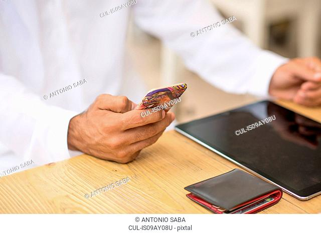 Close up of middle eastern man's hands using smartphone at cafe, Dubai, United Arab Emirates