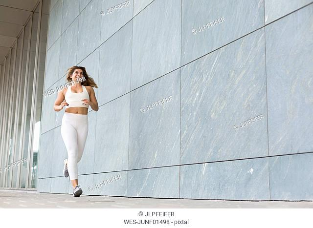 Jogging young woman dressed in white