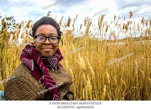 African American teenager girl dressed warm laughing and making a proud face in front of a wheat field at the palace, the Tryon Palace, New Bern, North Carolina