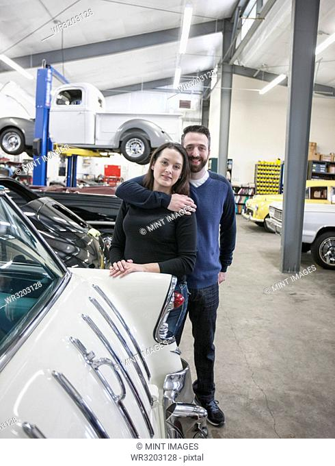 A couple, mechanics who work in a classic car auto repair shop. Man and woman