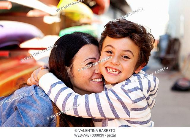 Spain, Barcelona, portrait of happy little boy hugging his mother