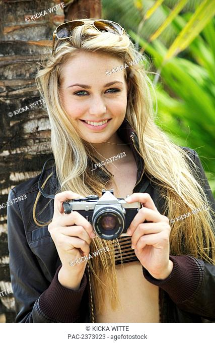A young woman posing with her camera; Kauai, Hawaii, United States of America