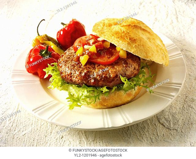 Home made burger in a crusty roll with tomato sweetcorn relish and omion and BBQ peppers