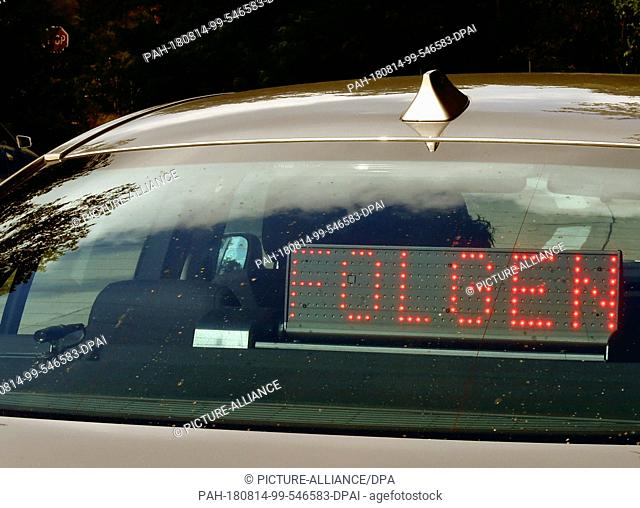 """14 August 2018, Ludwigsfelde, Germany: The writing """"""""Folgen"""""""" (lit. follow) lights up in the rear of a video car of the traffic police"""