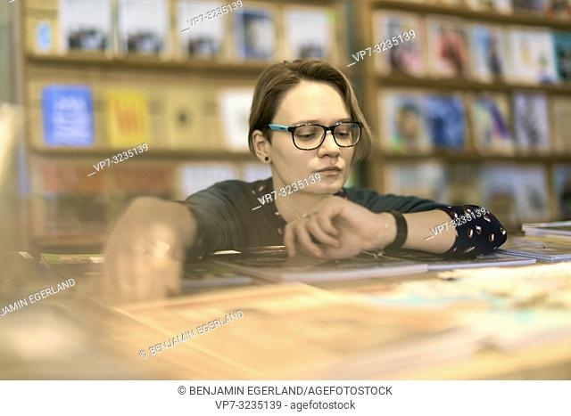 woman indoors in book store, in Munich, Germany