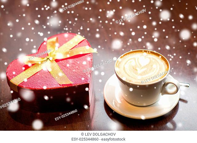 holidays, valentines day, love and drinks concept - close up of gift box and coffee cup on table over snow