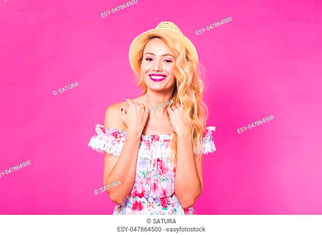 Portrait of a cheerful happy young woman on pink background. Summer, holidays and people concept