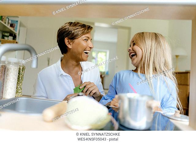Laughing mother and daughter playing with toy kitchen at home
