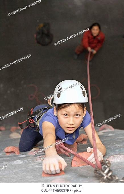Girl climbing indoor rock wall