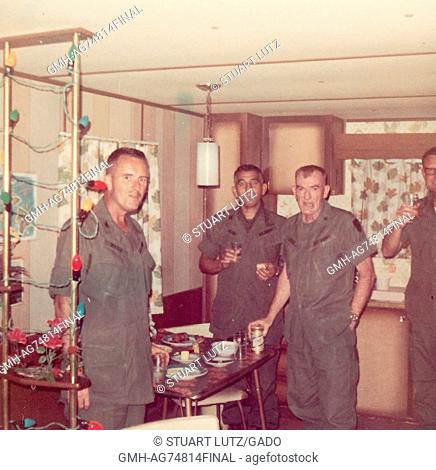 A photograph of United States Servicemen gathered inside the kitchen of a temporary housing unit in Vietnam, they are sharing food and drinks, 1968