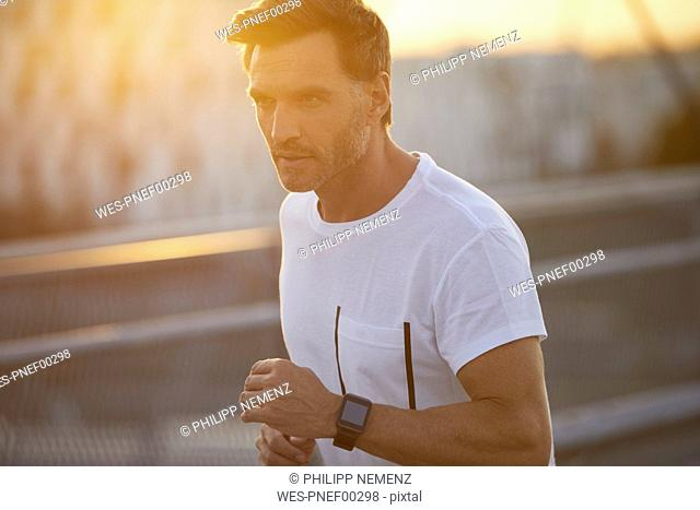 Man with smartwatch running in the city
