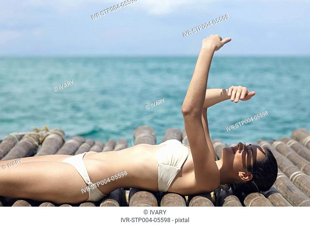A young woman lying on a dock by the ocean