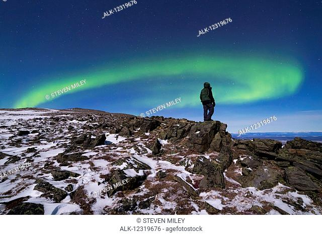 A man watches the aurora borealis from high on Donnelly Dome, south of Delta Junction