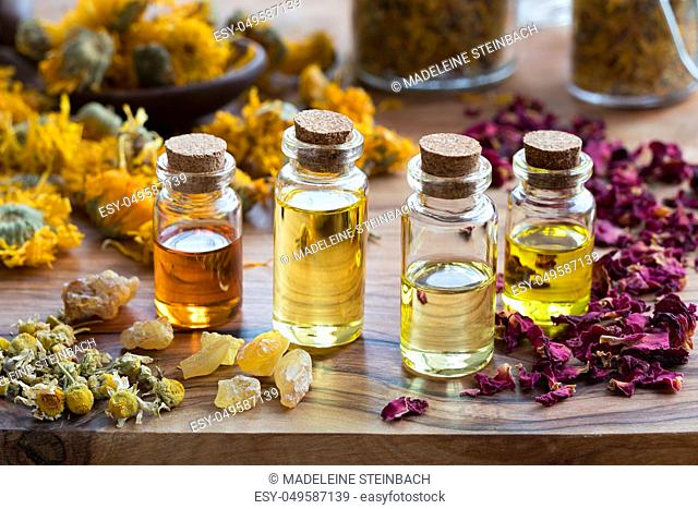 Bottles of essential oil with dried rose petals, chamomile, calendula and frankincense resin on a wooden background