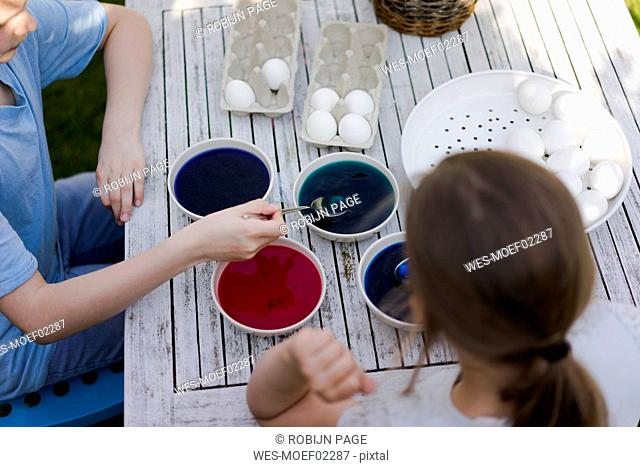 Two girls dyeing Easter eggs on garden table