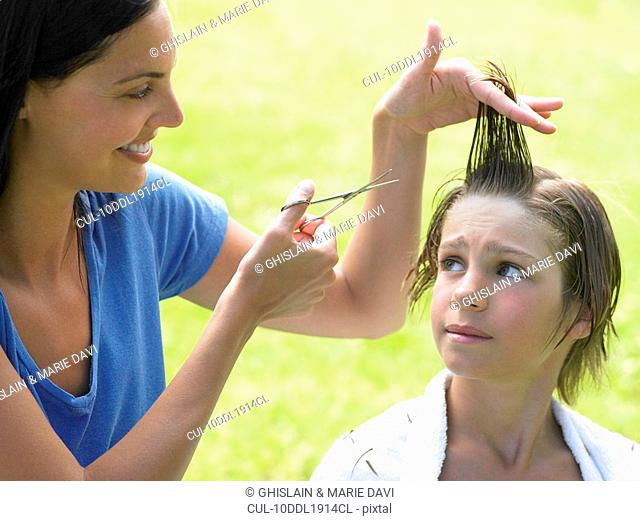 Boy gets his hair cut by woman