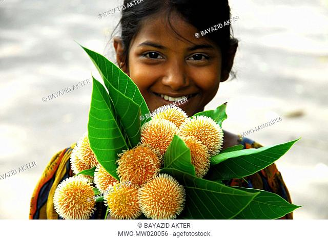 Portrait of a smiling girl who came to the Dhaka University Campus, to sell Kadam flowers, on the first day of the Bangla month Ashar rainy season Kadam flower...