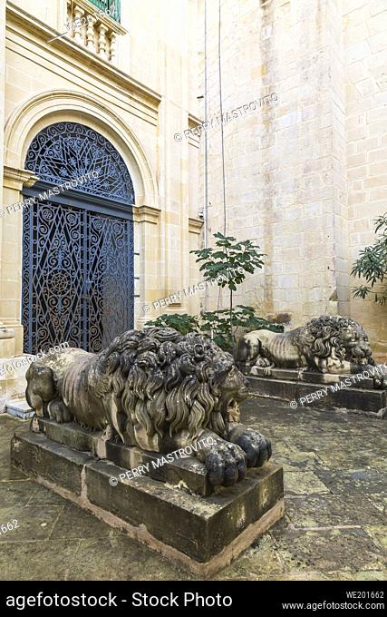 Carved limestone lion sculptures and arched entrance door with ornate wrought iron grills, Garden of the Grand Masters Palace, Valletta, Malta