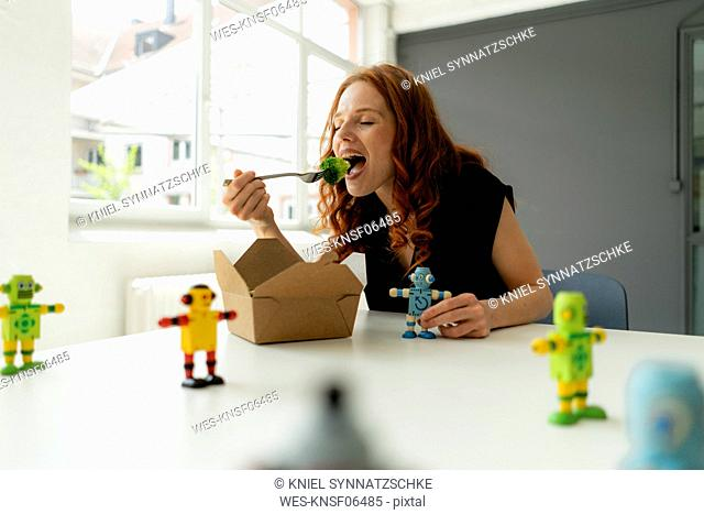 Portrait of redheaded businesswoman in a loft with miniature robots on desk eating healthy takeaway food