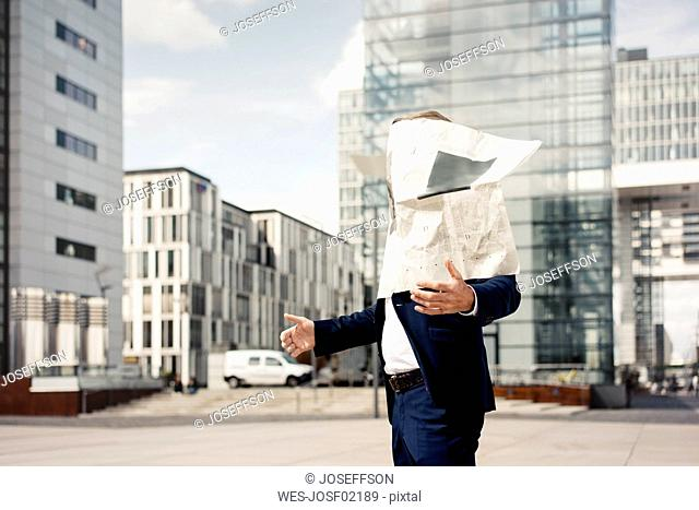 Newspaper covering businessman's face in the city