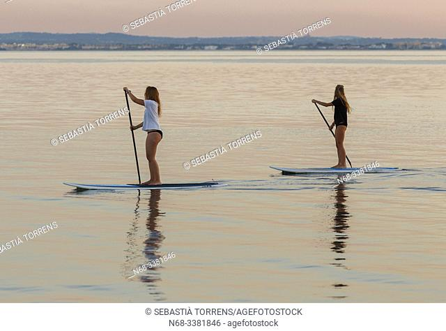 Two people practicing paddle surf at Alcanda at sunset, Alcudia, Majorca, Spain