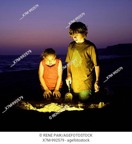 An adventurous boy and girl find treasure after digging on a sandy beach