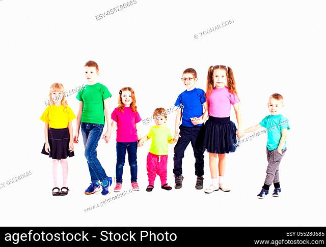 Children of different ages are standin and holging hands, wearing in rainbow t-shirts, isolated on white