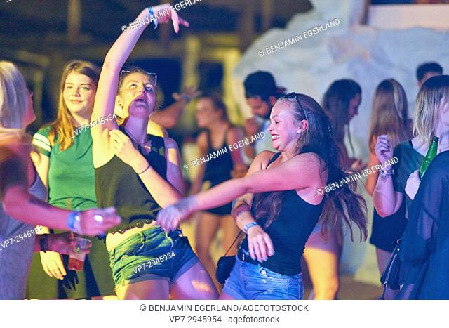 happy girls dancing at summer party at music festival. German ethnicity. At holiday destination Hersonissos, Crete, Greece