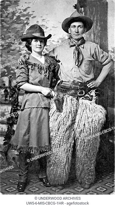 United States: c. 1900.A couple pose for a studio portrait in Western cowboy gear