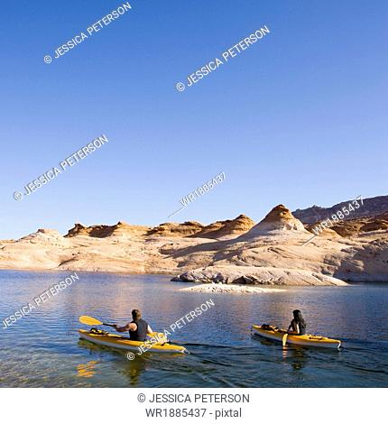 two people in kayaks on the lake