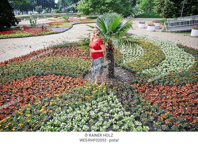 Happy pregnant woman standing amidst blooming flowers in park