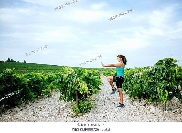 Woman doing tai chi in a vineyard