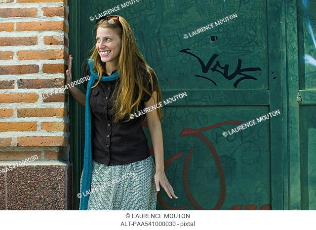 Young woman standing in alley, looking away, smiling