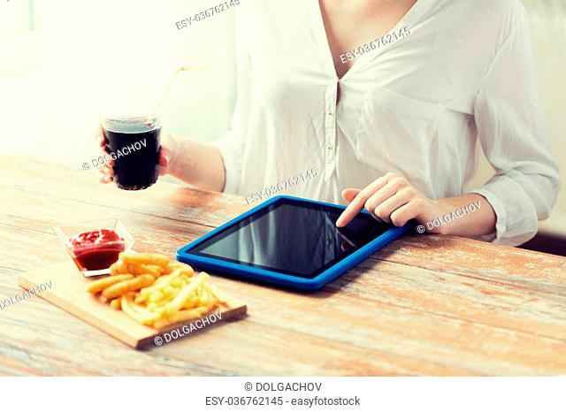 fast food, people, technology and diet concept - close up of woman with tablet pc computer eating french fries with ketchup