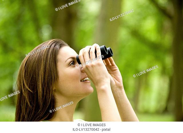 A young woman looking through binoculars, close-up