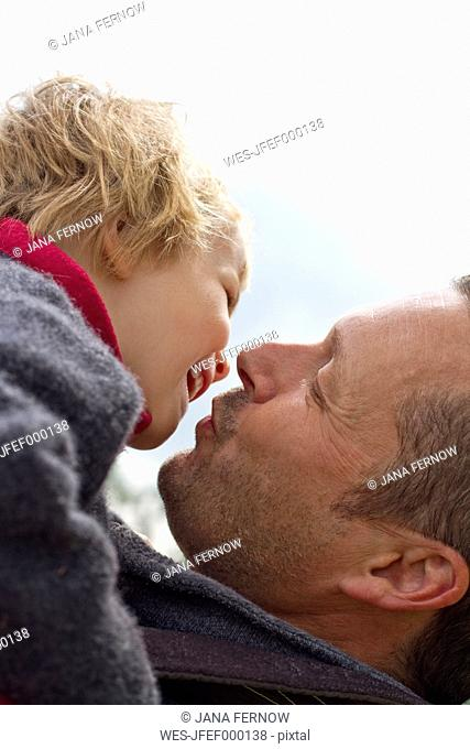 Germany, Kiel, Father kissing her daughter, close up