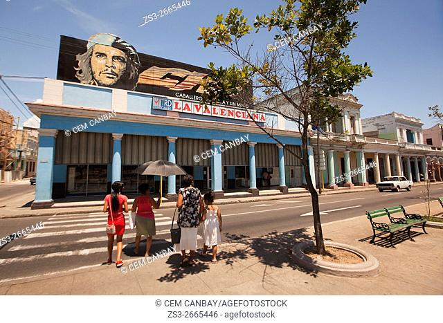 Pedestrian crossing the street with a picture of Ernesto Che Guevara at the background in Paseo del Prado or so called Boulevard, Cienfuegos, Cuba, West Indies