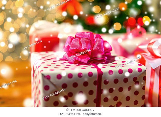 christmas, holidays, presents, new year and celebration concept - close up of gift boxes over christmas tree lights